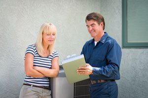 Homeowner discussing HVAC add-on products with service technician